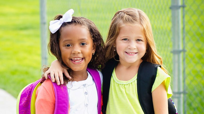 2 young girls smiling with backpacks