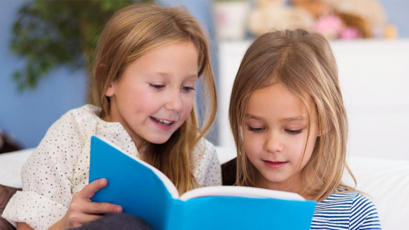 2 girls reading a book